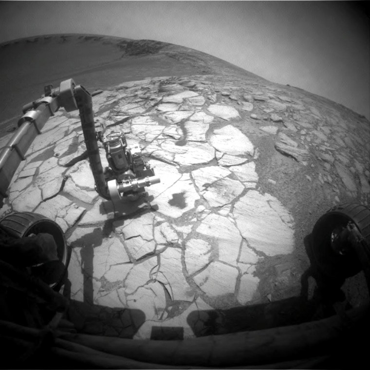 Opportunity used its front hazard-indentification camera to capture this wide-angle view of its robotic arm extended to a rock in a bright-toned layer inside the Victoria Crater.