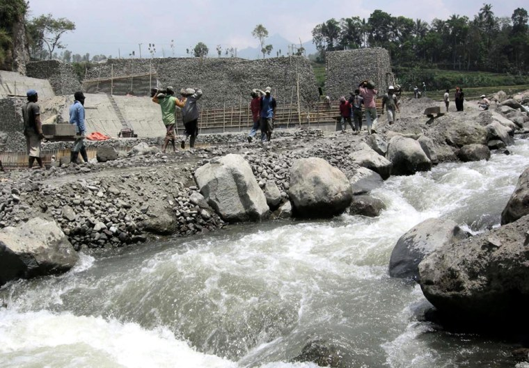 Laborers work on the site of a new dam in anticipation of the eruption of Mount Kelud volcano, at Tulungrejo village, Indonesia, on Oct. 5, with the volcano seen in the distance.