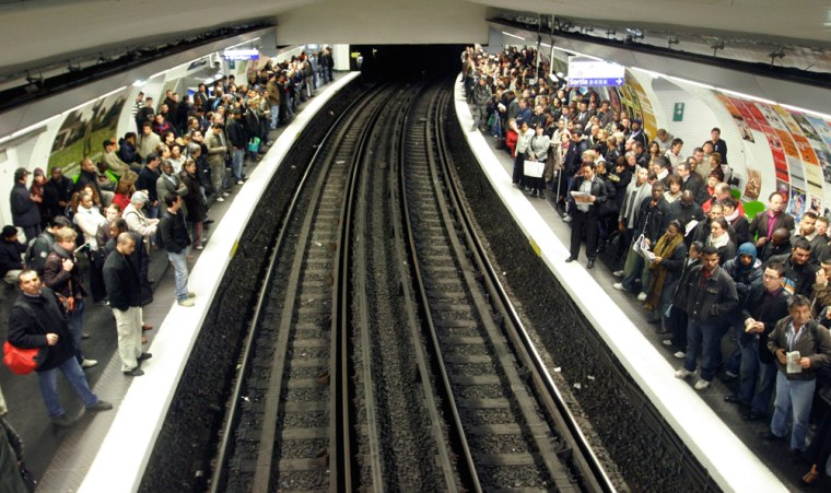 Subway users wait for a train in Paris on Friday. Train, subway and bus travel around France remained a tangle as Paris transit workers continued their walkoutover President Nicolas Sarkozy's economic reforms.
