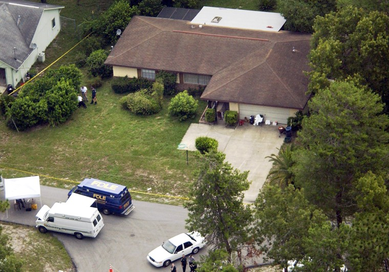 Investigators, at left, check the bushes in front of a home in Deltona, Fla., Friday, in which six bodies were found.
