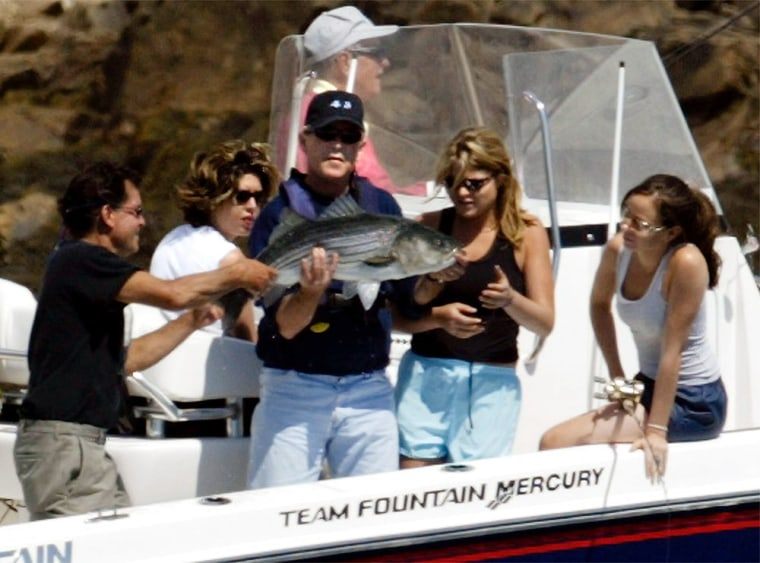 US President Bush holds fish caught by his daughter