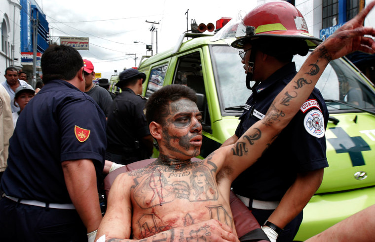Rescue workers carry a gang member injured during a riot at the El Hoyon prison in Escuintla, Guatemala, some 50 kilometers (30 miles) south of Guatemala City, on Monday.
