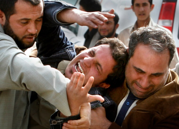 Men hold their cousin after his brother was killed in a suicide bomb attack in Baghdad