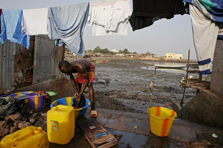 A man does his washing at a local fishing village at Conakry, Guinea. Entire neighborhoods in the capital haven't had electricity or running water for years.