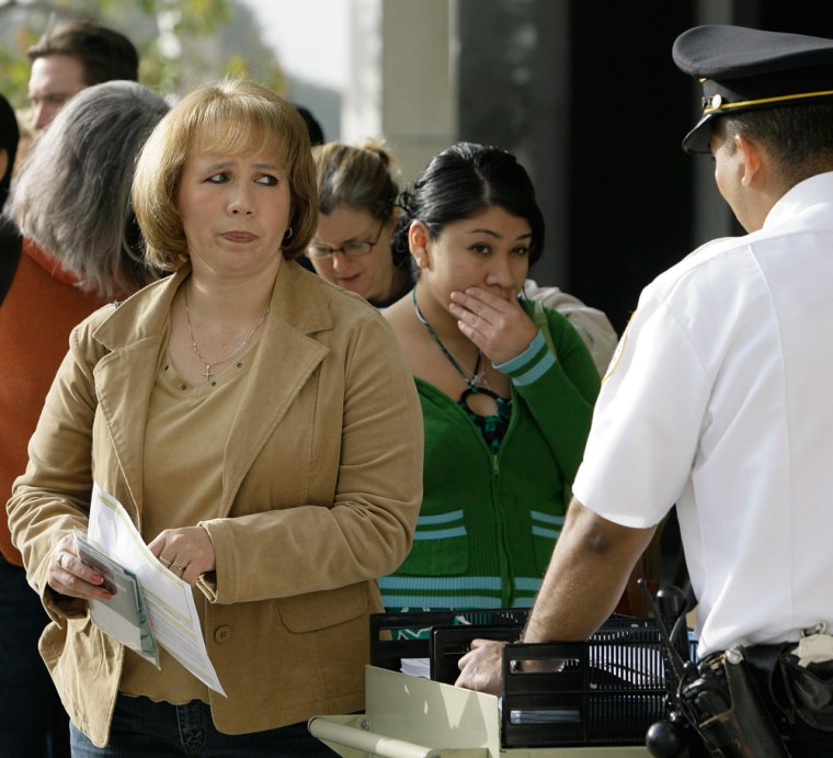 A passport seeker looks at an immigration official outside the U.S. Federal Building in Los Angeles, March 16. Overwhelmed by unprecedented demand, the State Department says the crush of new applicants has inundated its staff and caused delays of up to a month-and-a-half at the peak January-to-April season when many people are preparing to travel over the spring and summer.