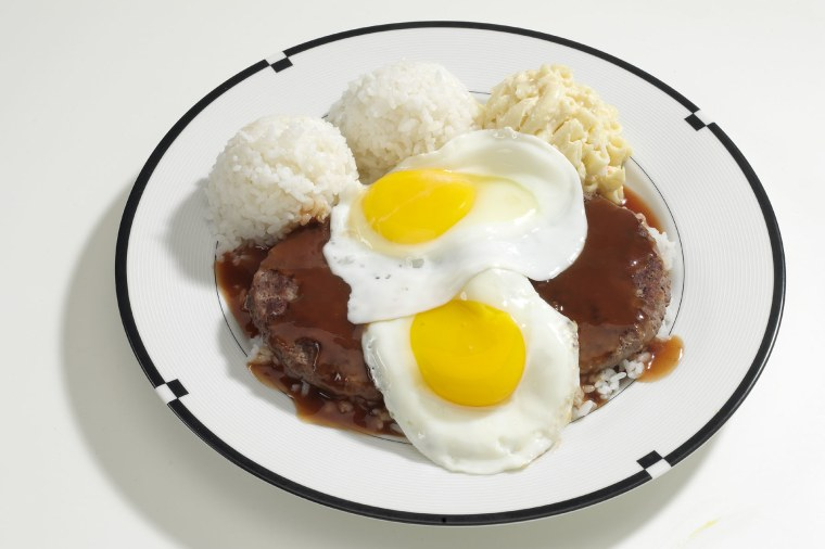 """Hawaiian Barbecue dish that is popular not only in Hawaii, but at a lot of our restaurants in the mainland. The dish is called the """"Loco Moco"""" and it's a concoction that includes an interesting twist to an American summer favorite – the hamburger. The dish includes two hearty pieces of Hawaiian Barbecued hamburger, topped with eggs and smothered with brown gravy."""