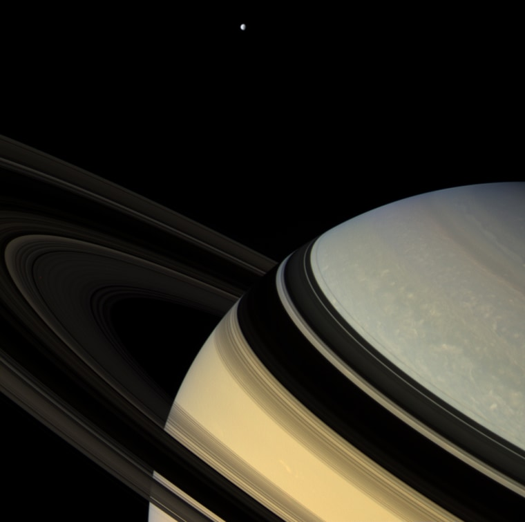 Magnificent blue and gold Saturn floats obliquely as one of its gravity-bound companions, Dione, hangs in the distance. The darkened rings seem to nearly touch their shadowy reverse images on the planet below.  This view looks toward the unlit side of the rings from about 9 degrees above the ring plane. The rings glow feebly in the scattered light that filters through them.  Dione is 1,126 kilometers (700 miles) across.  The image was taken in visible light with the Cassini spacecraft wide-angle camera on Feb. 4, 2007, at a distance of approximately 1.2 million kilometers (800,000 miles) from Saturn. Image scale is 75 kilometers (47 miles) per pixel.