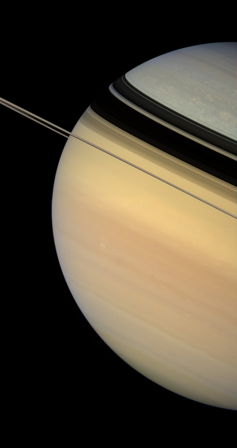 Dark and sharply defined ring shadows appear to constrict the flow of color from Saturn's warmly hued south to the bluish northern latitudes.  Scientists studying Saturn are not yet sure about the precise cause of the color change from north to south. NASA Voyager spacecraft flybys witnessed a more evenly painted planet in the early 1980s, when Saturn was closer to equinox. However, the bluish color was readily apparent upon Cassini's approach to the planet in late 2003, when Saturn was just coming out of its northern hemisphere winter. Scientists have speculated that the color is due to seasonal effects on the atmosphere.  Aside from the color differences, the cloud morphology is quite different in the polar regions compared to the mid-latitudes. Bright, isolated clouds dot the high latitudes, while Saturn's middle is characterized by flowing cloud bands and the occasional bright or dark vortex.  This view looks toward the lit side of the rings from about half a degree below the ring plane.  Images taken using red, green and blue spectral filters were combined to create this natural-color view. The images were obtained with the Cassini spacecraft wide-angle camera on Feb. 4, 2007, at a distance of approximately 1.2 million kilometers (700,000 miles) from Saturn. Image scale is 67 kilometers (42 miles) per pixel.