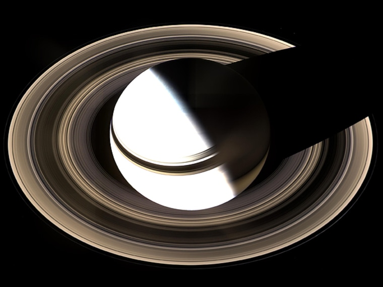 Surely one of the most gorgeous sights the solar system has to offer, Saturn sits enveloped by the full splendor of its stately rings.  Taking in the rings in their entirety was the focus of this particular imaging sequence. Therefore, the camera exposure times were just right to capture the dark-side of its rings, but longer than that required to properly expose the globe of sunlit Saturn. Consequently, the sunlit half of the planet is overexposed.  Between the blinding light of day and the dark of night, there is a strip of twilight on the globe where colorful details in the atmosphere can be seen. Bright clouds dot the bluish-grey northern polar region here. In the south, the planet's night side glows golden in reflected light from the rings' sunlit face.  Saturn's shadow stretches completely across the rings in this view, taken on Jan. 19, 2007, in contrast to what Cassini saw when it arrived in 2004 (see PIA05429 </catalog/PIA05429>).  The view is a mosaic of 36 images -- that is, 12 separate sets of red, green and blue images -- taken over the course of about 2.5 hours, as Cassini scanned across the entire main ring system.  This view looks toward the unlit side of the rings from about 40 degrees above the ring plane.  The images in this natural-color view were obtained with the Cassini spacecraft wide-angle camera at a distance of approximately 1.23 million kilometers (764,000 miles) from Saturn. Image scale is 70 kilometers (44 miles) per pixel.