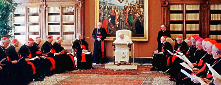** RETRANSMITTING TO ADD IDENTIFICATIONS ** Pope John Paul II reads his message to American cardinals gathered in his private library in Vatican City, Tuesday, April 23, 2002. From left to right, clockwise, Cardinal Adam Joseph Maida of Detroit, Cardinal Theodore McCarrick of Washington D.C., Cardinal Francis Eugene George of Chicago, Cardinal Anthony Joseph Bevilacqua of Philadelphia, Cardinal Roger Micheal Mahony of Los Angeles, Cardinal Bernard Law of Boston, Vatican Secretary of State Cardinal Angelo Sodano, papal aide Bishop James Harvey, Pope John Paul II, Monsignor Bryan Chestle (standing), U.S. Cardinal William Wakefield Baum, U.S. Cardinal Edmund Casimir Szoka, U.S. Cardinal Avery Dulles, Cardinal William Henry Keeler of Baltimore, Cardinal Edward Egan of New York, Monsignors Wilton Gregory and William Skylstad, President and Vice President respectively of the American Conference of Catholics Bishops, Cardinal Jorge Arturo Medina Estevez of Chile,  U.S. Cardinal James Francis Stafford, president of the Pontifical Council of the U.S., and Vatican Prefect for Catholic Education Cardinal Zenon Grocholewski of Poland. (AP Photo/Arturo Mari)