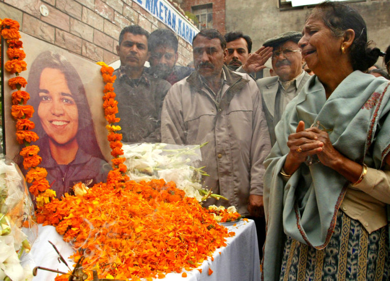 Image: Subesh Chawla weeps in front of a picture