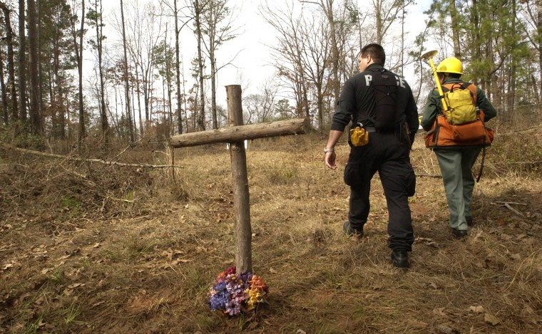 Image: Searchers pass a makeshift memorial