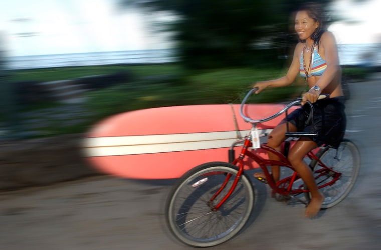 SURFER BIKES WITH HER SURF BOARD