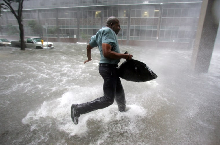 Arnold James tries to keep his feet as a strong gust nearly blows him over as he tries to make his way on foot to the Louisiana Superdome in New Orleans on Monday, Aug. 29, 2005.  The roof on James's home blew off, forcing him to seek shelter at the Superdome. (AP Photo/Dave Martin)