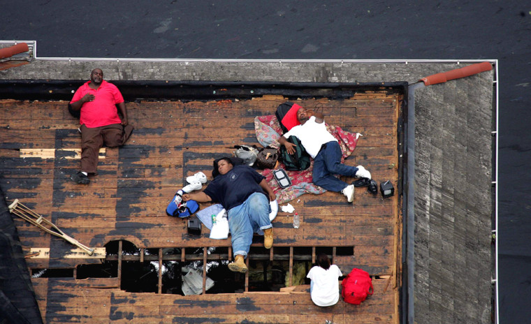 Residents wait on a roof top to be rescued from the floodwaters of Hurricane Katrina in New Orleans.