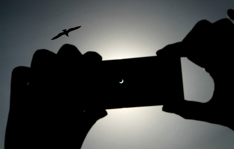A man looks at the annular eclipse of th