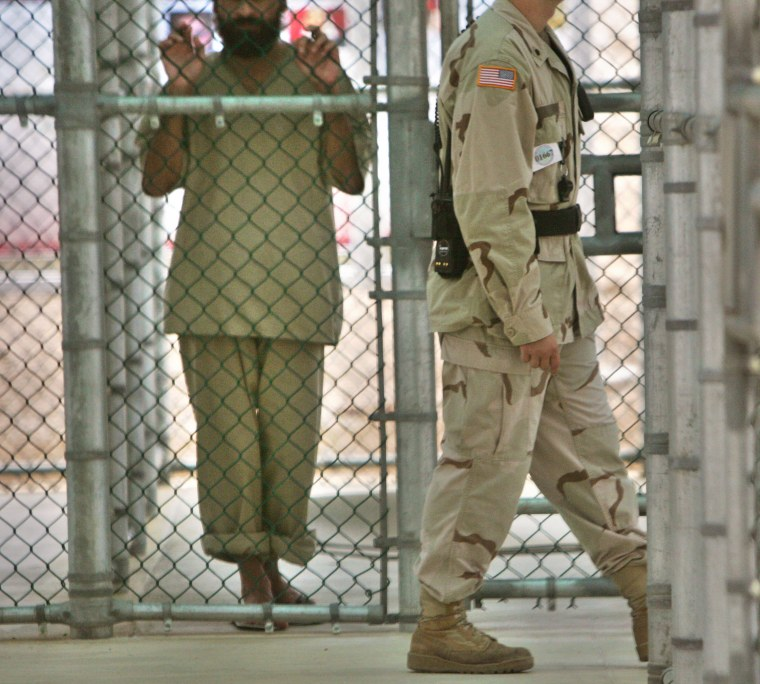 In this photo, reviewed by US military officials, a detainee at the Camp 5 maximum security prison at Guantanamo Bayholds onto a fence as a U.S. military guard walks past.