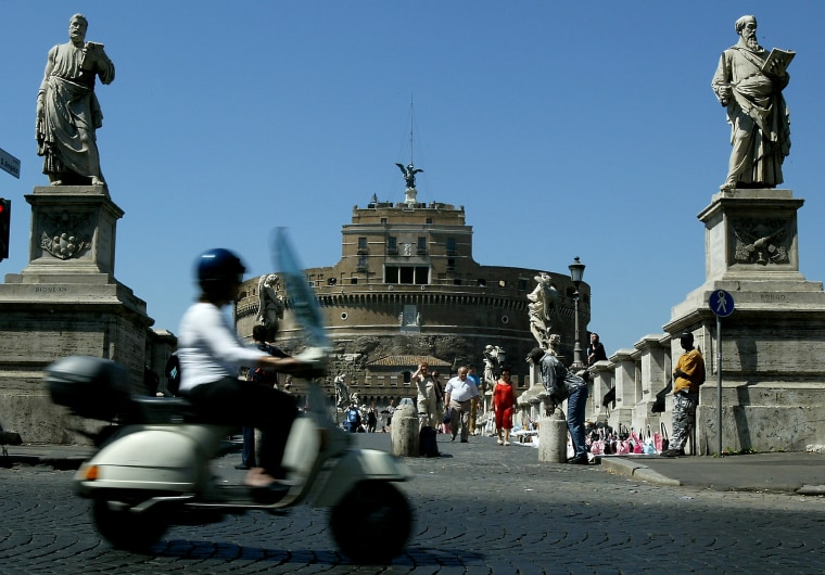 Woman Rides a Scooter as she Passes the Castel Sant'Angelo