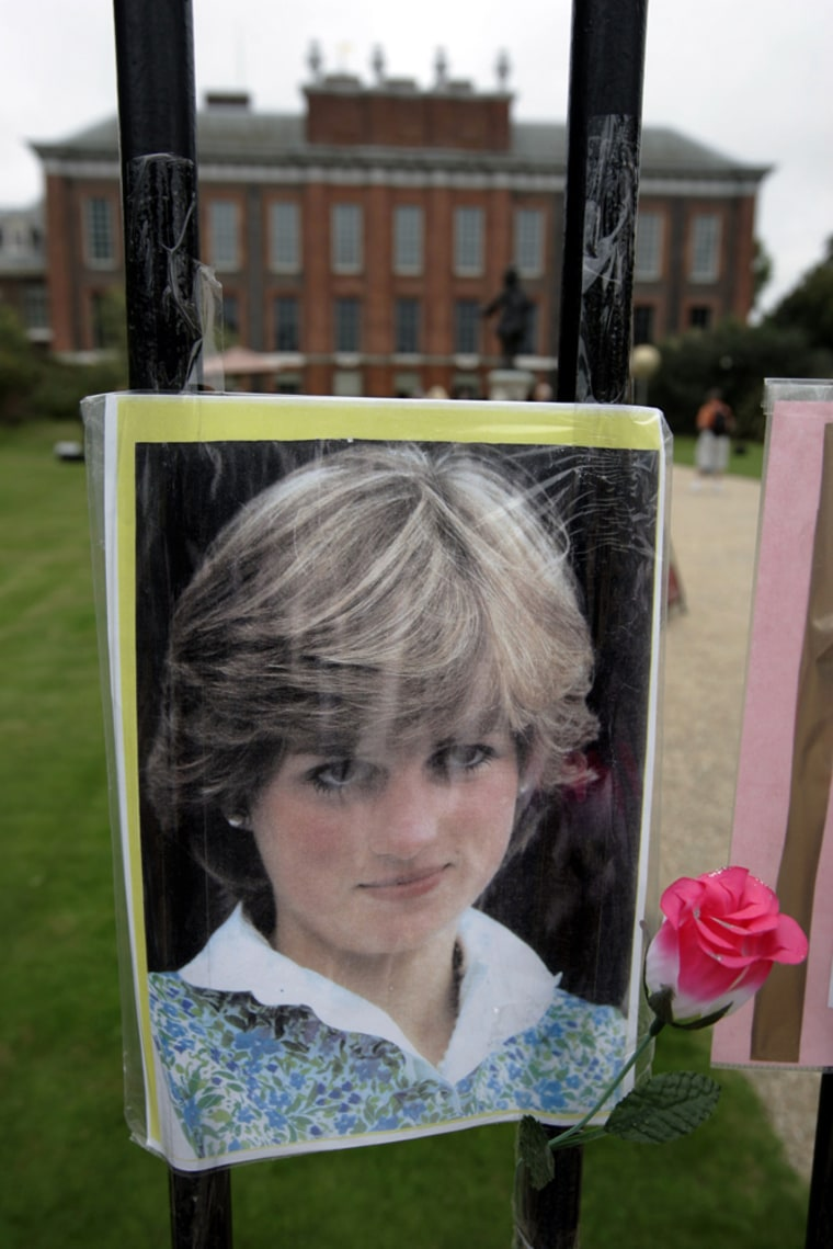 A photograph and a plastic flower in memory of late Princess Diana, is seen within the grounds of Kensington Palace in London, the day before a memorial service will be held to mark 10 years since her death, Thursday, Aug. 30, 2007. It has been 10 years since her death in a Paris car crash, when many Britons were poleaxed by grief for a vivacious and troubled woman who was at once princess, style icon, charity worker and tabloid celebrity. (AP Photo/Lefteris Pitarakis)
