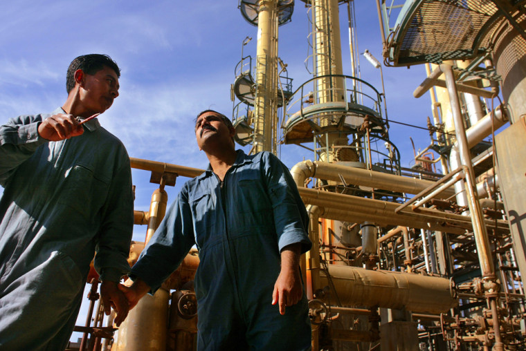 Two Iraq oil workers walk through the Dura oil refinery outside Baghdad Saturday, Feb. 22, 2003. Iraq's oil reserves are the second largest in the world after Saudi Arabia. (AP Photo/Jerome Delay)
