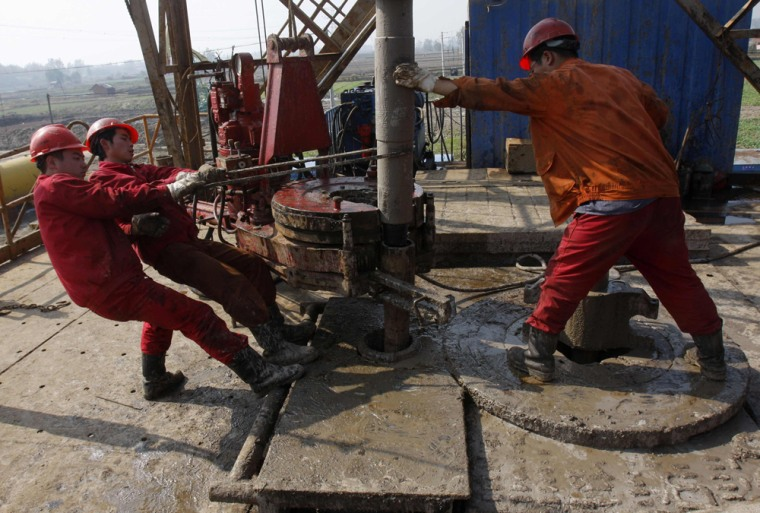 Oil field workers work at a well head in Sinopec's Jianghan oil field on the outskirts of Guanghua