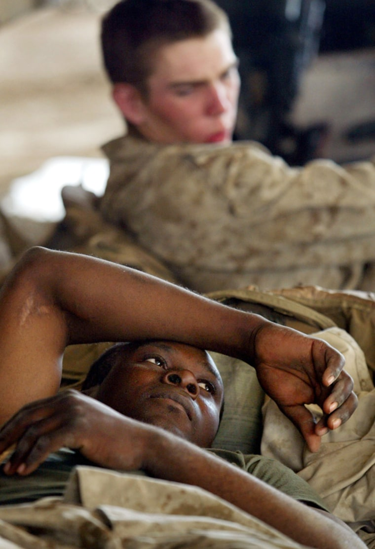 U.S. Marines Adelphin Angervil of Miami, Fla., below, and Charles Williams of Lafayette, Ind., rest Tuesday in their camp in Fallujah, Iraq, after coming under fire.