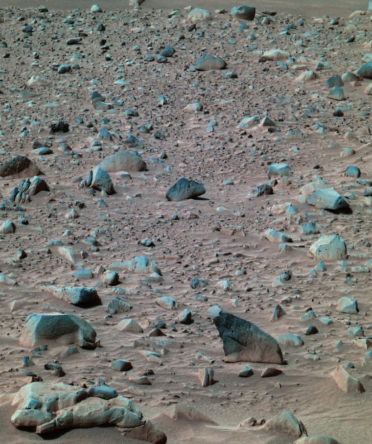 "A ""stretched-color"" image shows the Spirit rover's rocky surroundings within Mars' Gusev Crater. Variations in color have been exaggerated to highlight differences in geological composition."