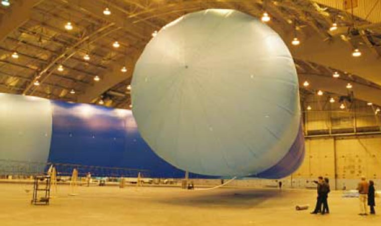 Onlookers are dwarfed by the 175-foot-long, V-shaped Ascender airship within JP Aerospace's hangar. The propeller-driven craft is filled with helium and is designed to rise to altitudes beyond 100,000 feet.