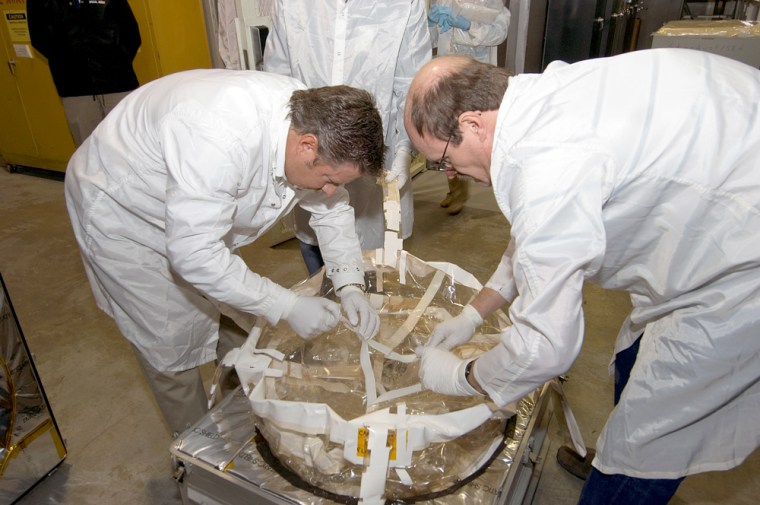 Steve Glenn and Ron Seeders examine the Stardust sample canister at NASA's Johnson Space Center, where the comet samples and interstellar dust will be curated.