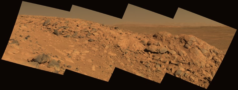 "A mosaic of images from NASA's Spirit rover shows a rock outcrop dubbed ""Longhorn,"" with the sweeping plains of Gusev Crater in the background. On the horizon, the rim of Gusev Crater is clearly visible."