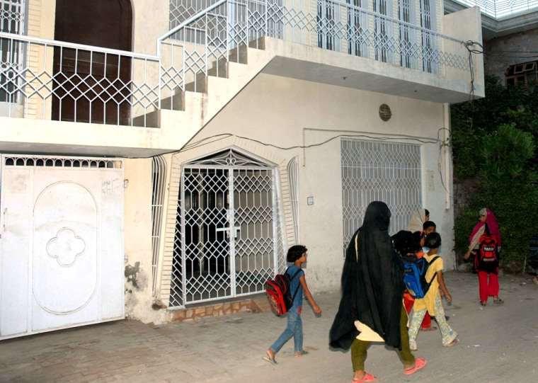 Pakistani students walk past the house believed to be that of Rashid Rauf, an alleged leader in the reported plot to blow up jetliners bound for the United States with liquid explosives.
