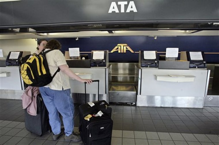 Travelers arrive at an empty ATA check-in counter on April 3, in L.A., only to discover that the airline had discontinued all operations.