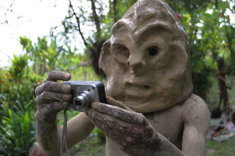 A Chimbu Mudman checks out an HP digital camera