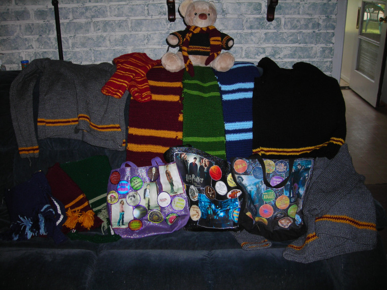 A picture of some of the harry Potter stuff that i have knit and croched. It includes 2 gryffindor house sweaters, 1 gryffindor scarf, one gryffindor sweater vest, one gryffindor knitted purse, 1 slytherin scarf and one slytherin knitted purse, one ravenclawscarf and one ravenclaw knitted purse, three purses that i made using iron on transfers, and a teddy bear wearing a gryffindor scarf and sweater, both of which i croched.