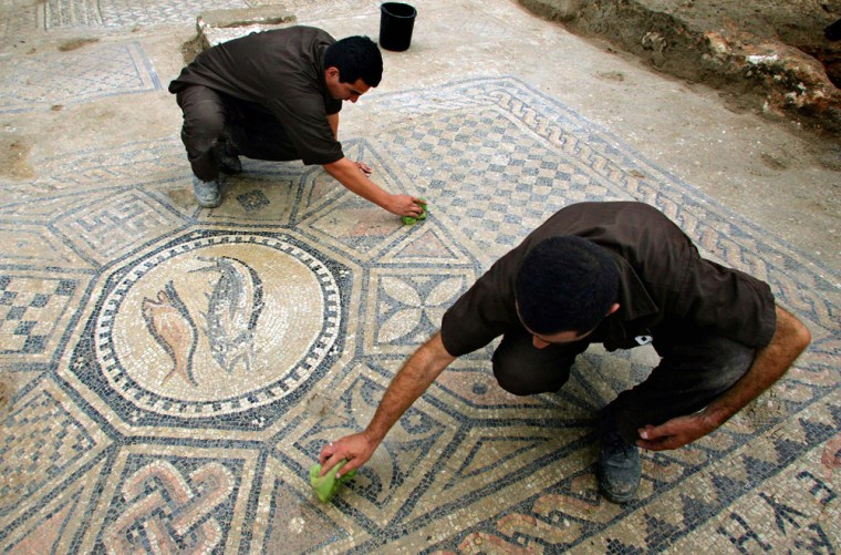 Israeli prisoners Rizlov Ramil, top, and Biton Maymon, bottom, clean a section of a Christian mosaic floor dating to the third or fourth century A.D., in the compound of the Megiddo prison in northern Israel.