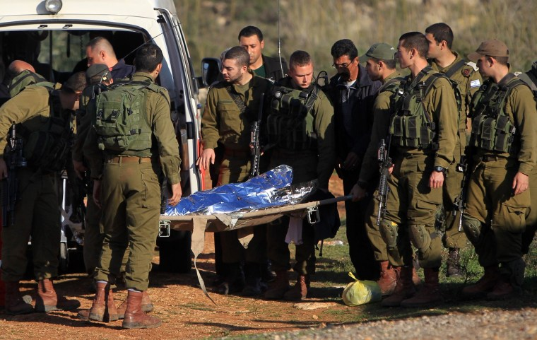 Israeli soldiers evacuate the body of Oman Dwekat, a 17-year-old Palestinian who was shot dead by Israeli troops during a stone-throwing incident, on December 29, 2014 near the Tapuah settlement, south of the West Bank city of Nablus. The Israeli army said soldiers had fired warning shots before opening fire on a group throwing stones at Israeli civilians. AFP PHOTO / JAAFAR ASHTIYEHJAAFAR ASHTIYEH/AFP/Getty Images