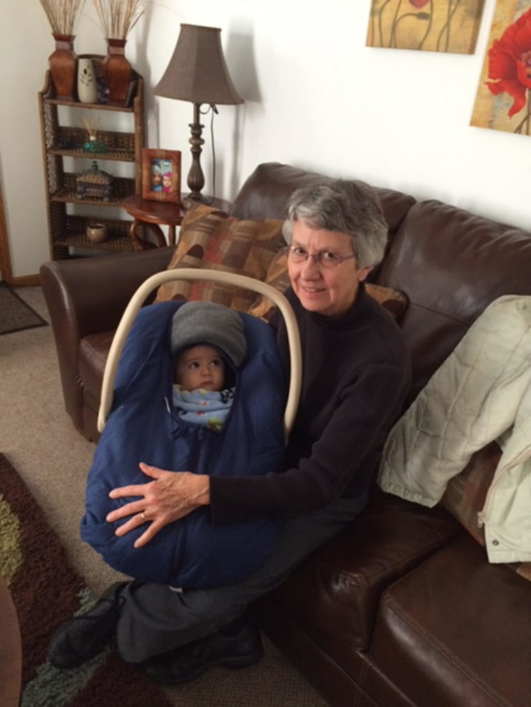 Sister Judy Stephens feeding a nine-month-old infant and she prepares to take the baby and his mother to an appointment to get financial assistance to buy food.
