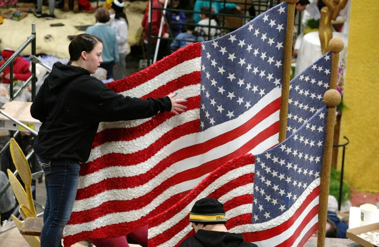 Image: A woman works on a Rose Parade float at the Rose Palace in Pasadena, California