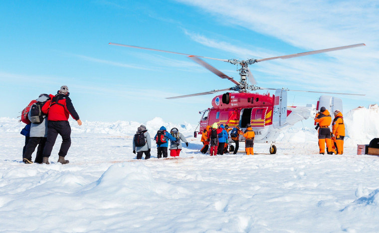 Image: A helicopter from Chinese icebreaker Xue Long picks up passengers from the stranded Russian ship MV Akademik Shokalskiy