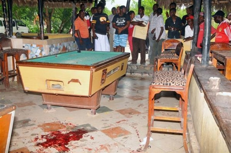 Image: People look at stains on the floor next to a pool table at the Tanduri Bar and Night Club in Ukunda, Kenya