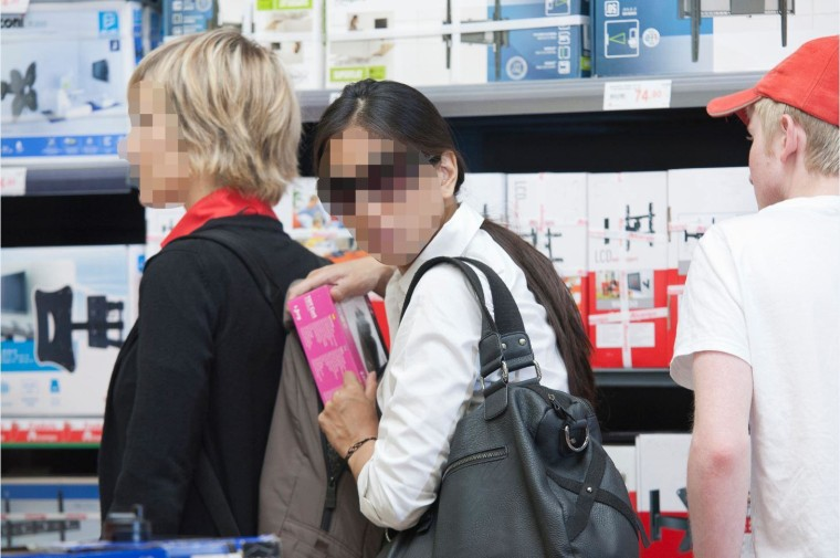 Shoplifting incidents rise around the holidays, and experts say the culprits are often seeking an emotional boost. In this photo illustration, two women steal electronics. Editor's note: The subjects' faces have been intentionally blurred.