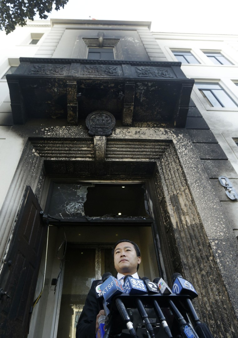 Wang Chuan, spokesman for the Chinese Consulate, speaks outside of the damaged entrance to the consulate in San Francisco on Thursday, Jan. 2, 2014.