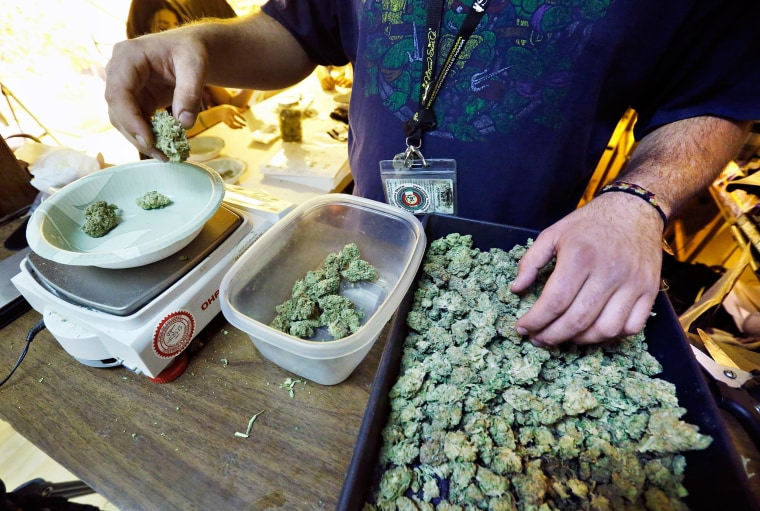 Image: An employee weighs portions of marijuana at a Denver shop