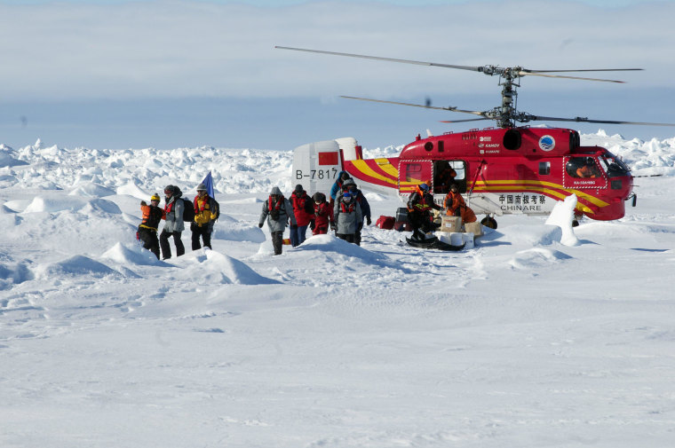 Image: A helicopter unloads rescued passengers from the Akademik Shokalskiy, in East Antarctica.
