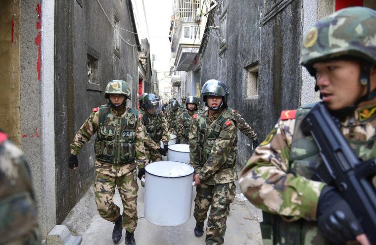 Image: Paramilitary policemen carry seized crystal meth at Boshe village