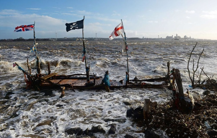 Waves pour over 'The Black Pearl', a model pirate ship made from driftwood, in New Brighton in northwest England, on Jan. 3, 2014. High tides and strong winds caused flooding in parts of England on Friday as severe flood warnings remained in place.