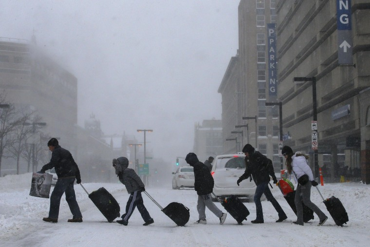 Image: Travelers leave Back Bay train and subway station during winter nor'easter snow storm in Boston