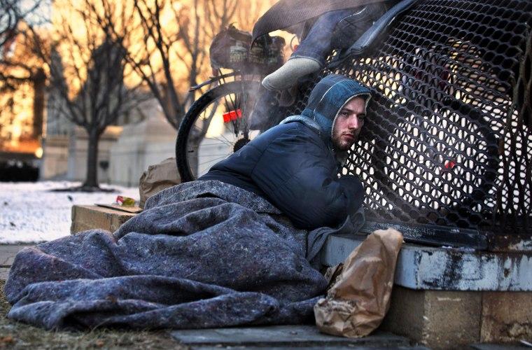 Image: Nicholas Simmons, 20, of Greece, N.Y.,  warms himself on a steam grate