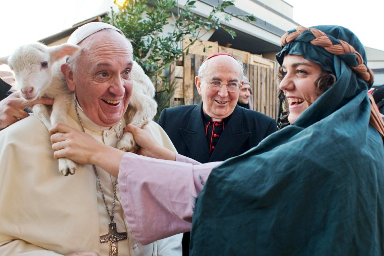 Image: A woman dressed as a character from a nativity scene puts a lamb around the neck of Pope Francis.