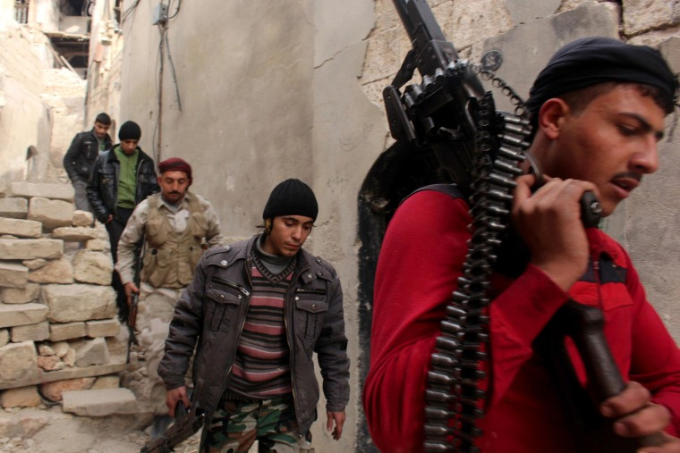 Image: Free Syrian Army fighters walk with their weapons
